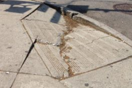 Image of cracked, uneven curb cut.