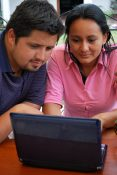 Young Hispanic/Latino couple looking at their laptop.
