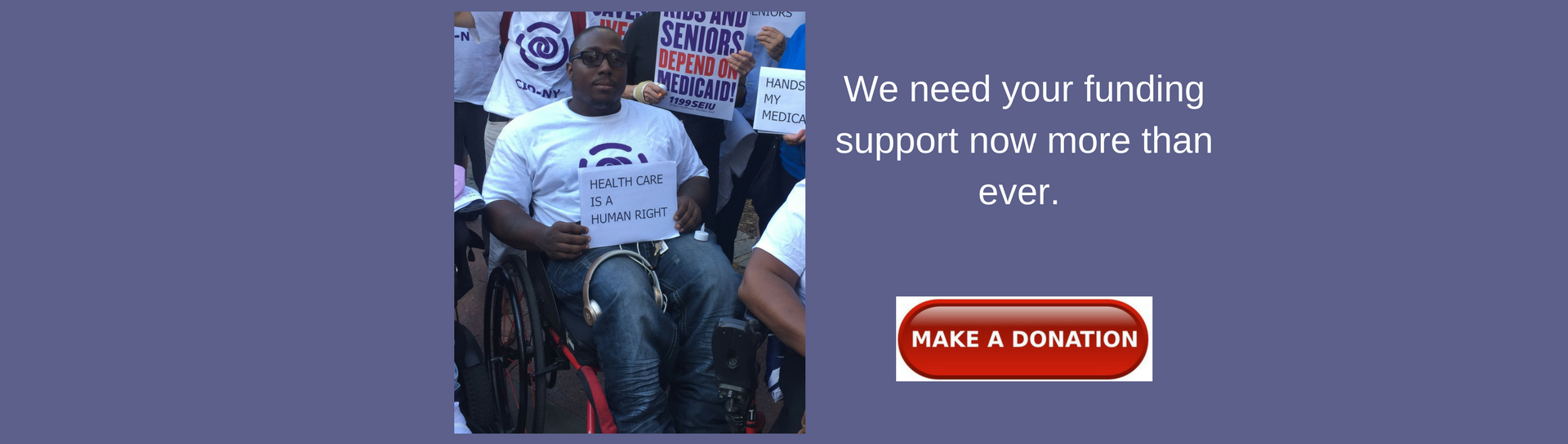 Image of Dustin, a wheelchair user, with sign saying
