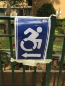 Voting sign taped to a fence with an icon of a wheelchair user and an arrow facing the opposite way.