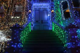 View of entrance to home covered in Christmas lights.