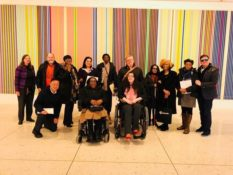 Group photo of advocates at Lobby Day in Albany with a multi-colored striped painting the background.