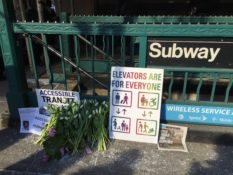 Memorial in front of subway station for Malaysia Goodson, with flowers and signs calling for accessibility.